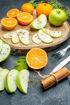 Onderaanzicht appel en mandarijn plakjes op houten bord kaneelstokjes vork en mes op zwarte tafel