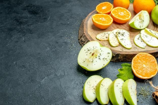 Onderaanzicht appel en mandarijnen plakjes op houten bord kaneelstokjes gedroogd muntpoeder op zwarte tafel kopieerplaats