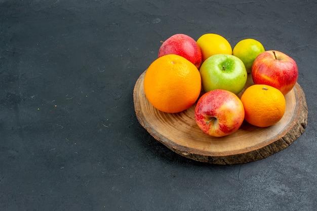 Onderaanzicht appels citroen sinaasappels op een houten bord op een donkere ondergrond vrije plaats surface