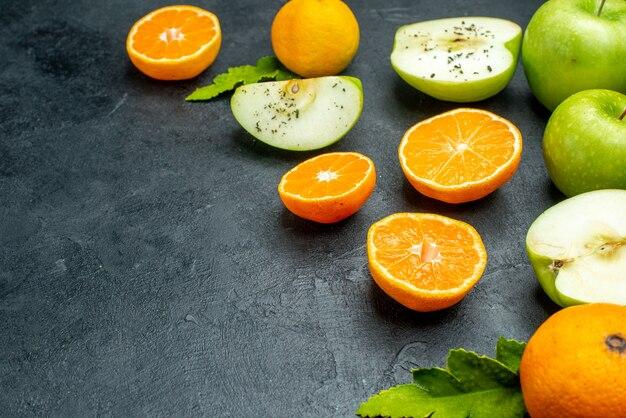 Onderaanzicht appels en mandarijnen plakjes bladeren op zwarte tafel met kopieerruimte
