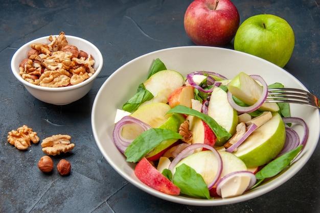 Onderaanzicht appelsalade in kom appelschijfje op vork walnoot in kom rode en groene appels op donkere tafel