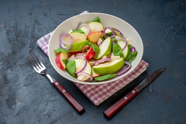 Onderaanzicht appelsalade in kom roze en wit geruit servet een vork en mes op donkere tafel
