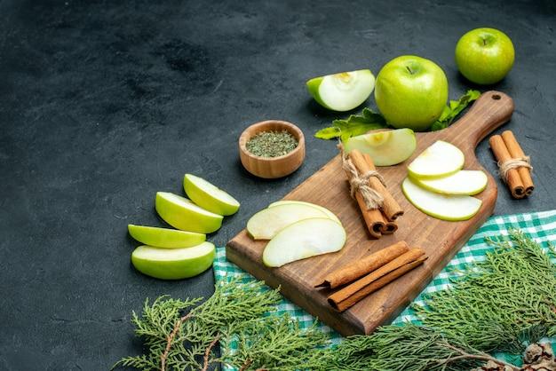 Onderaanzicht appelschijfjes en kaneel op houten bord gedroogd muntpoeder in kom appels groen en wit geruit tafelkleed dennenboomtakken op zwarte grond vrije plaats