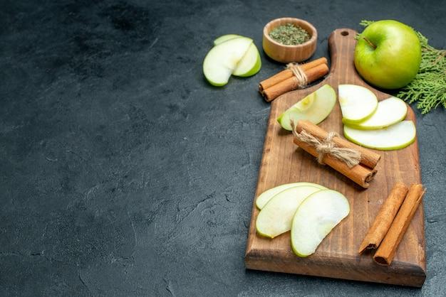 Onderaanzicht appelschijfjes en kaneelstokjes op houten serveerplank gedroogd muntpoeder in kleine kom op donkere tafel met kopieerplaats