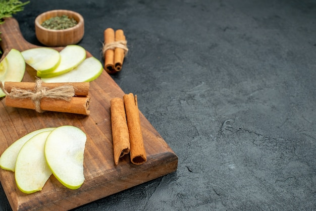 Onderaanzicht appelschijfjes en kaneelstokjes op snijplank mes en vork gedroogd muntpoeder in kom op donkere tafel met vrije ruimte