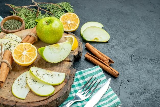 Onderaanzicht appelschijfjes gebonden kaneelstokjes en citroenschijfjes appel met munt op houten bord dennenboomtakken een vork en mes op groen servet op zwarte tafel met kopieerplaats
