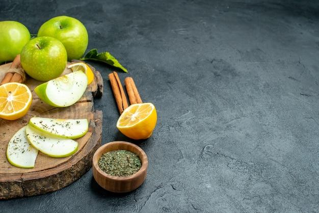 Onderaanzicht appelschijfjes kaneel en citroenschijfjes appel op houten bord gesneden citroen kaneel gedroogde munt in kleine kom op zwarte tafel met kopieerruimte