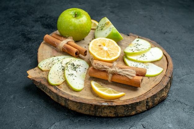 Onderaanzicht appelschijfjes kaneel en citroenschijfjes op een houten bord met gedroogde muntpoederappel op zwarte grond