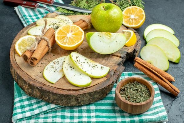 Onderaanzicht appelschijfjes kaneelstokjes en citroenschijfjes appel op een houten bord een vork en mes op groen servet op zwarte grond