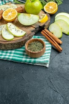 Onderaanzicht appelschijfjes kaneelstokjes en citroenschijfjes appel op een houten bord op groen servet op zwarte tafel met vrije plaats