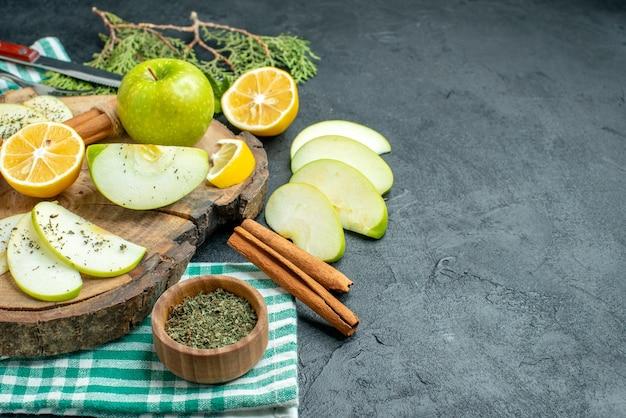 Onderaanzicht appelschijfjes kaneelstokjes en citroenschijfjes appel op houten bord dennenboomtakken gedroogde muntkom op groen servet op zwarte tafel vrije ruimte