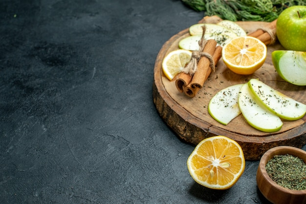 Onderaanzicht appelschijfjes kaneelstokjes en citroenschijfjes appel op houten plank pijnboomtakken een vork en mes gesneden citroen gedroogde munt op zwarte tafel met vrije plaats