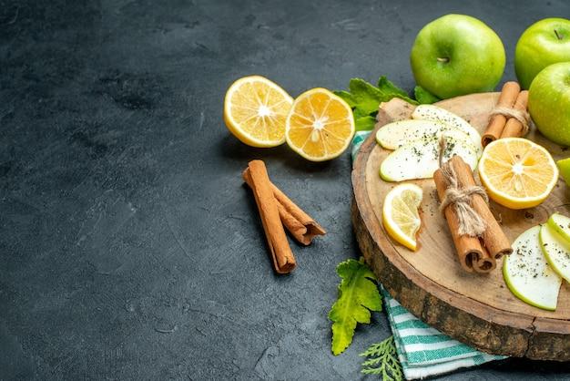 Onderaanzicht appelschijfjes kaneelstokjes en citroenschijfjes op een houten bord gesneden citroenen appels op zwarte tafel met vrije ruimte
