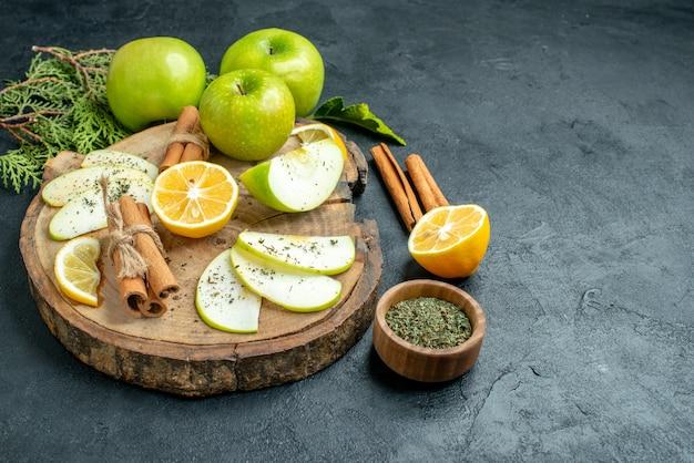 Onderaanzicht appelschijfjes kaneelstokjes en schijfjes citroen appel op een houten bord gesneden citroen kaneel gedroogde munt in kleine kom op zwarte tafel met kopieerruimte