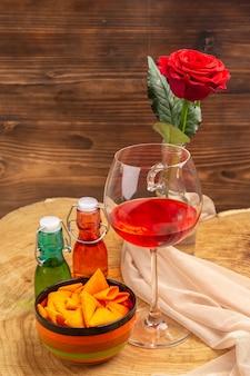 Onderaanzicht ballon wijnglas chips in kom rode en groene flessen rode roos op bruin oppervlak