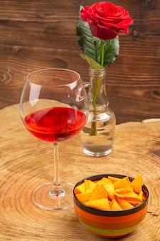 Onderaanzicht ballon wijnglas chips in kom rode roos op bruin oppervlak