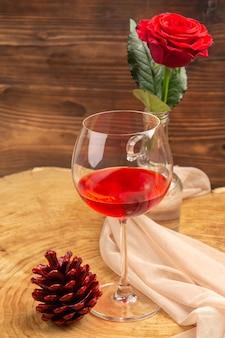 Onderaanzicht ballon wijnglas rode dennenappel rode roos op bruin oppervlak