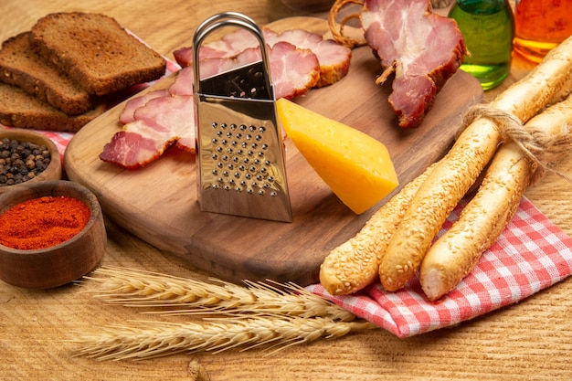Onderaanzicht becon plakjes kaasrasp op snijplank brood tarwe spike rode en zwarte peper in kleine kom op bruin oppervlak