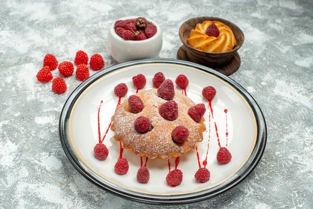 Onderaanzicht bessencake op wit ovaal bordkoekje in houten kom frambozen in kom op grijs oppervlak
