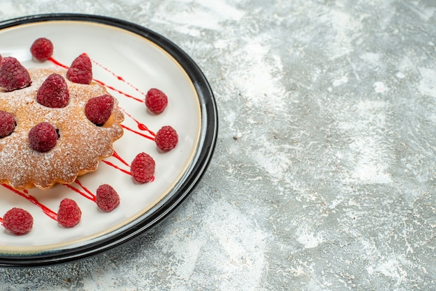 Onderaanzicht bessencake op witte ovale plaat op grijs oppervlak met kopieerruimte