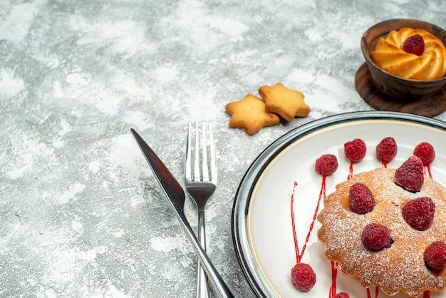 Onderaanzicht bessencake op witte ovale plaatkoekjesvork en dinermes op grijs oppervlak