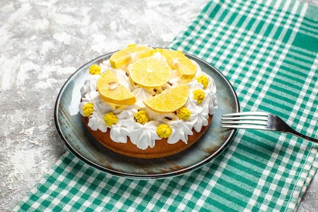 Onderaanzicht cake met banketbakkersroom en citroenvork op schotel op groen wit geruite tafel