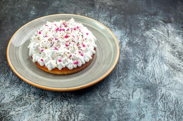 Onderaanzicht cake met banketbakkersroom op grijze ronde schotel op grijze tafel