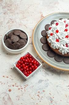 Onderaanzicht cake met banketbakkersroom op ovale plaatbessen en chocolade in kommen op beige tafel