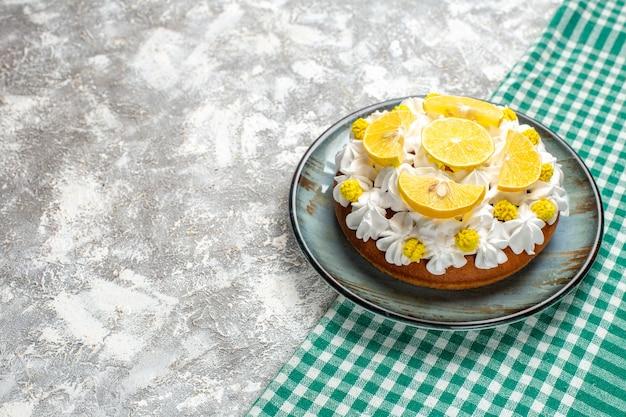 Onderaanzicht cake met witte banketbakkersroom en schijfjes citroen op ronde plaat op groen en wit geruite tafel