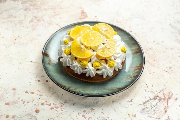 Onderaanzicht cake met witte banketbakkersroom en schijfjes citroen op ronde plaat op lichtgrijze tafel