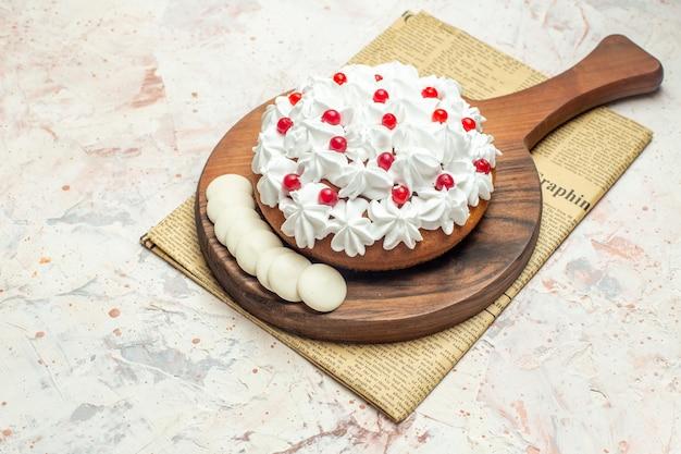 Onderaanzicht cake met witte banketbakkersroom en witte chocolade op snijplank op krant op lichtgrijze tafel