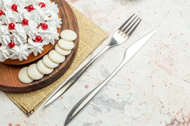 Onderaanzicht cake met witte banketbakkersroom op een houten bord op krantenvork en dinermes op lichtgrijze tafel