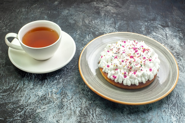 Onderaanzicht cake met witte banketbakkersroom op grijze ronde schotel kopje thee op grijze tafel