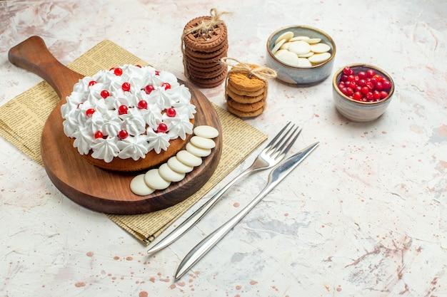 Onderaanzicht cake met witte banketbakkersroom op houten bord op krantenvork en diner mes bessen en witte chocolade in kommen cookies vastgebonden met touw op lichtgrijze tafel
