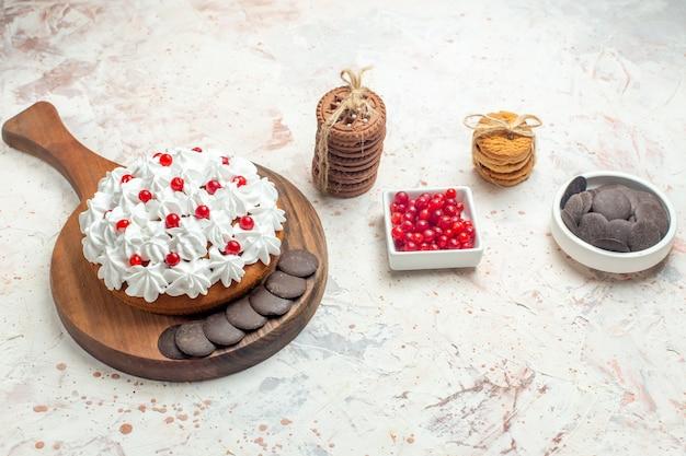 Onderaanzicht cake met witte banketbakkersroom op snijplankkom met bessen en chocoladekoekjes vastgebonden met touw op lichtgrijze tafel