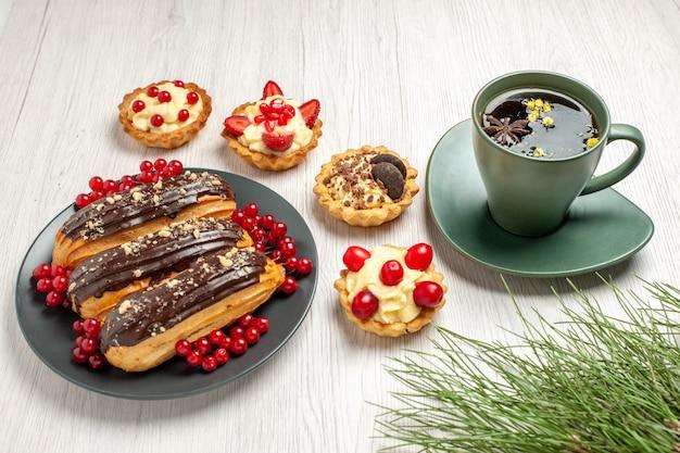 Onderaanzicht chocolade eclairs en aalbessen op de grijze plaat omgeven met taartjes een kopje thee en dennenboom bladeren op de witte houten tafel