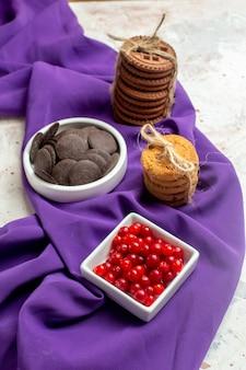 Onderaanzicht chocolade en bessen in kommen paarse sjaalkoekjes vastgebonden met touw op witte tafel