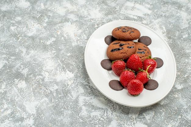 Onderaanzicht chocoladekoekjes aardbeien en ronde chocolaatjes op het witte ovale bord aan de rechterkant van de grijs-witte achtergrond