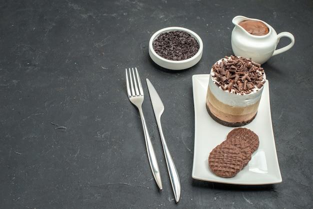 Onderaanzicht chocoladetaart en koekjes op witte rechthoekige plaatkom met chocoladevork en mes op donkere geïsoleerde achtergrond met vrije ruimte
