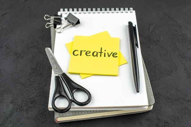 Onderaanzicht creatief geschreven op gele notitie schaar zwarte penbinder clips op notebook op donkere achtergrond