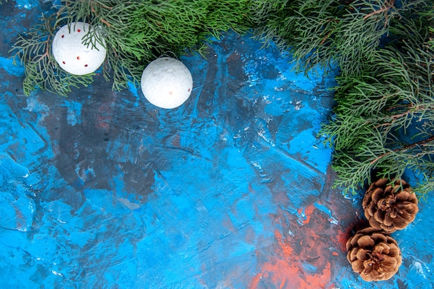 Onderaanzicht dennenboom takken dennenappels wit kerstboom speelgoed op blauw-rode achtergrond met vrije ruimte
