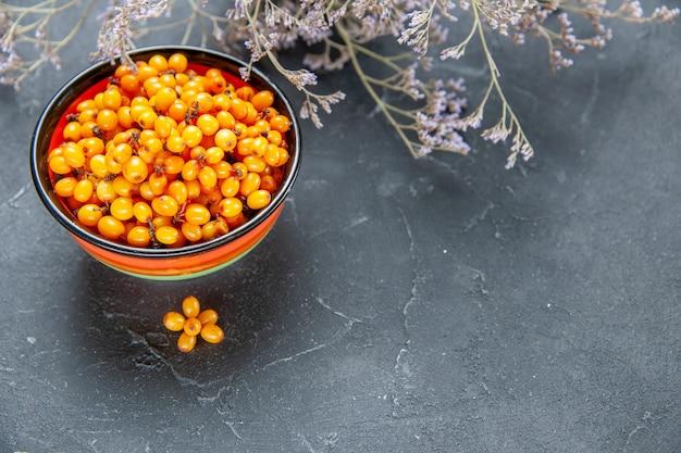 Onderaanzicht duindoorn in kom gedroogde bloemtak op donkerrood oppervlak vrije plaats