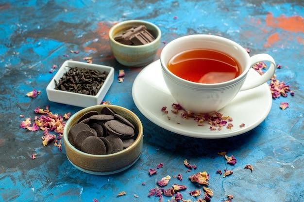 Onderaanzicht een kopje thee verschillende gevormde chocolaatjes in kleine kommen op blauw rood oppervlak