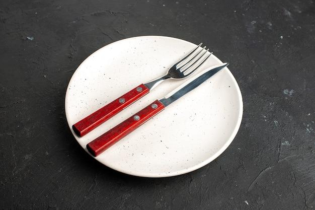 Onderaanzicht een vork en mes op een witte saladeplaat op een zwarte ondergrond