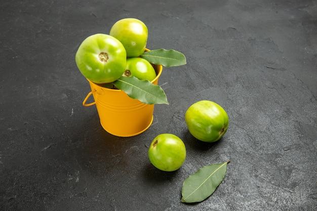 Onderaanzicht emmer groene tomaten en laurierblaadjes en tomaten op donkere achtergrond