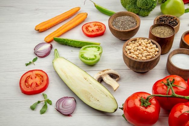 Onderaanzicht erwten met zwarte ogen en kruiden in kleine kommen, gesneden groenten, tomaten op witte tafel