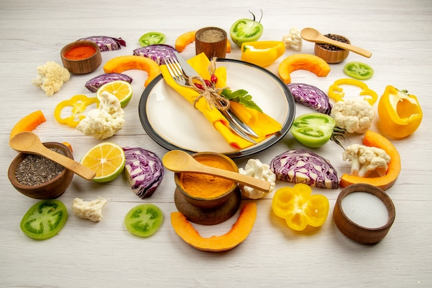 Onderaanzicht gebonden mes en vork met gele servet op ronde schotel gesneden groenten rode kool pompoen bloemkool gele paprika kruiden in kleine kommen op witte houten tafel
