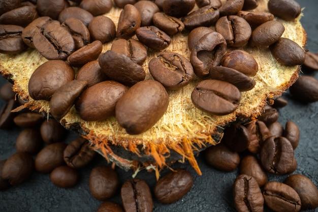 Onderaanzicht gebrande koffie zaden op houten bord op donkere achtergrond