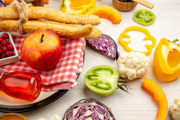 Onderaanzicht gehakte groenten appelbrood rode fles op servet op ronde plaat op witte tafel