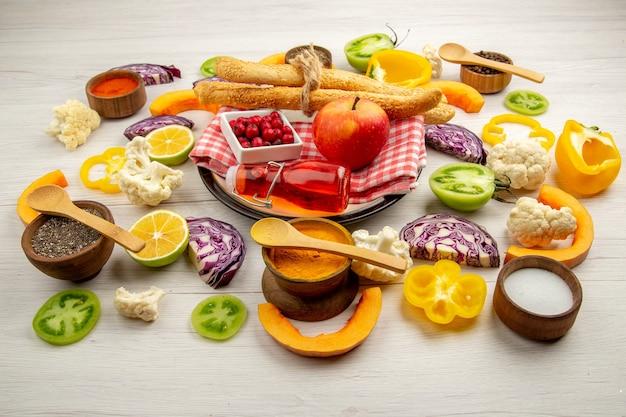 Onderaanzicht gehakte groenten appelbrood rode fles op servet op witte schotel verschillende kruiden in kleine kommen op tafel